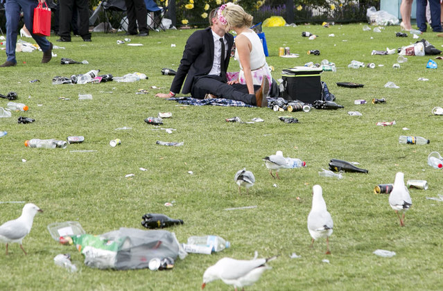 A couple kiss surrounded by rubbish at the conclusion of the races during the Emirates Melbourne Cup Day held at Flemington Racecourse in Melbourne Australia, on November 4, 2014. (Photo by Asanka Brendon/Rex Features)