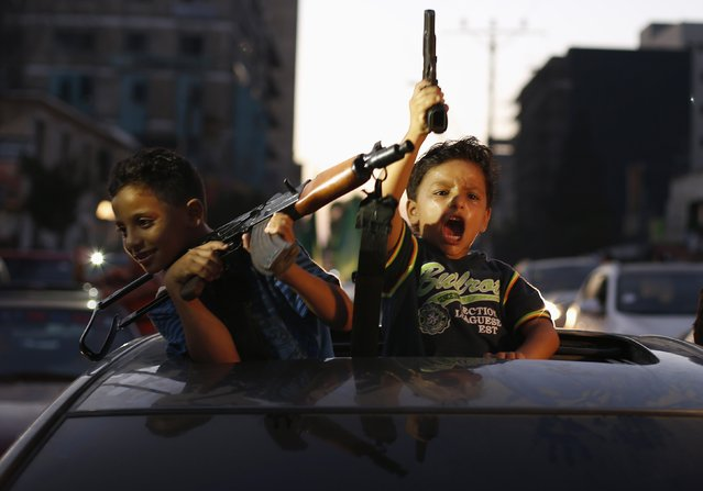 Palestinian children hold guns as they celebrate with others what they said was a victory over Israel, following a ceasefire in Gaza City in this August 26, 2014 file photo. I was covering the celebrations by Palestinians moments after the declaration of a ceasefire that ended a 51-day fighting between Israel and Hamas. Throwing sweets and chanting slogans, people took to the streets, riding vehicles and motorcycles, to celebrate what they said was victory over Israel. (Photo and caption by Suhaib Salem/Reuters)