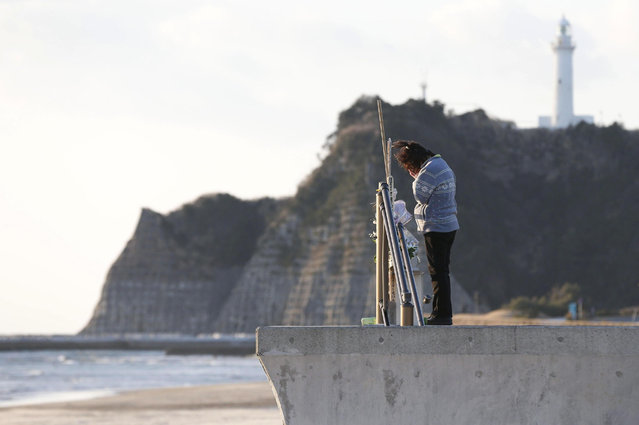A woman on the coast of Tairausuiso in Iwaki, Fukushima Prefecture, prays Monday for family members killed in the earthquake and tsunami on March 11, 2011.  (Photo by KYODO)