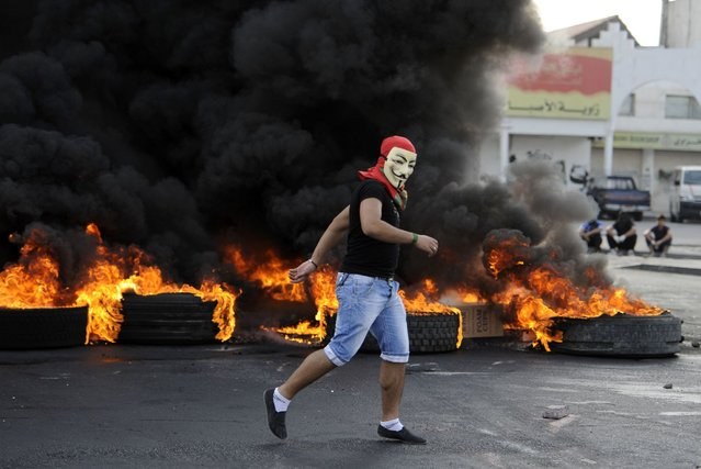 A protester burns tires to set up road blocks in the village of Sanabis during clashes with riot police, west of Manama, March 14, 2013. (Photo by Hamad I Mohammed/Reuters)