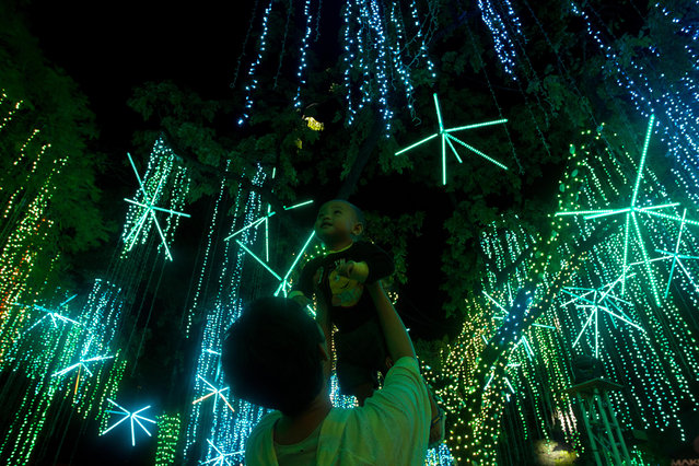 People enjoy a lights and sounds show on November 24, 2014 in Makati City, Philippines. The Philippines is the earliest country known to celebrate Christmas.  (Photo by Mark Cristino/Barcroft Media)