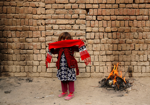 A girl stands next to a fire on a cold winter morning in Kabul, Afghanistan on December 10, 2017. (Photo by Mohammad Ismail/Reuters)