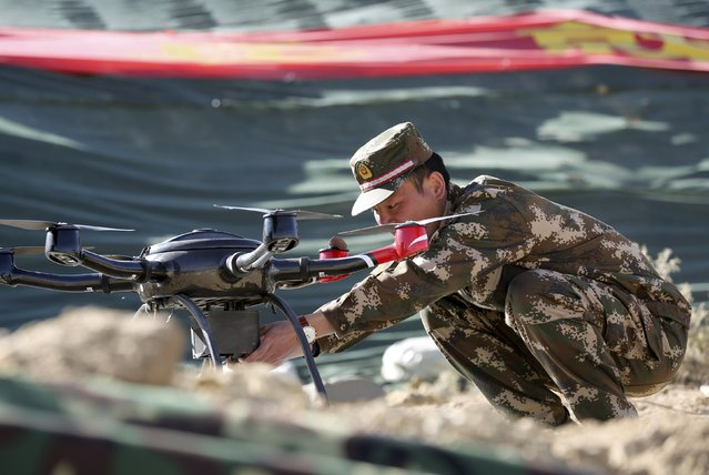 A police officer prepares a drone for display during a drill at a military base in Shigatse, Tibet Autonomous Region, China, October 25, 2015. (Photo by Reuters/Stringer)