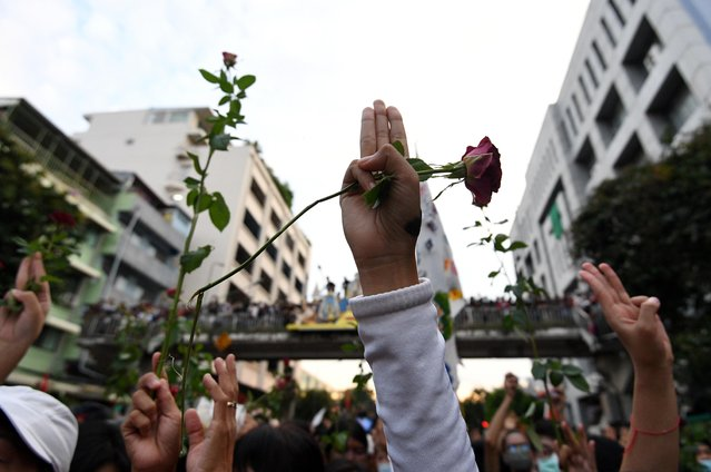 A pro-democracy demonstrator flashes a three-finger salute while holding up a rose during a Thai anti-government mass protest, on the 47th anniversary of the 1973 student uprising, in Bangkok, Thailand on October 14, 2020. (Photo by Chalinee Thirasupa/Reuters)