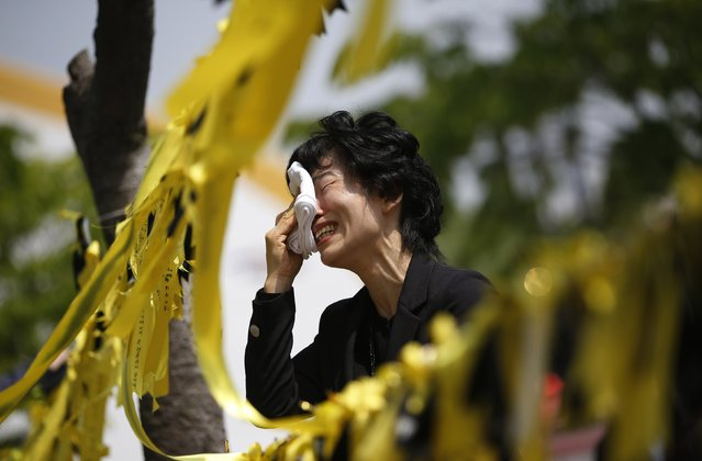 A mourner cries next to yellow ribbons dedicated to missing and dead passengers of the sunken Sewol passenger ship, after paying tribute at the official memorial altar in Ansan, in this May 2, 2014 file photo. (Photo by Kim Hong-Ji/Reuters)