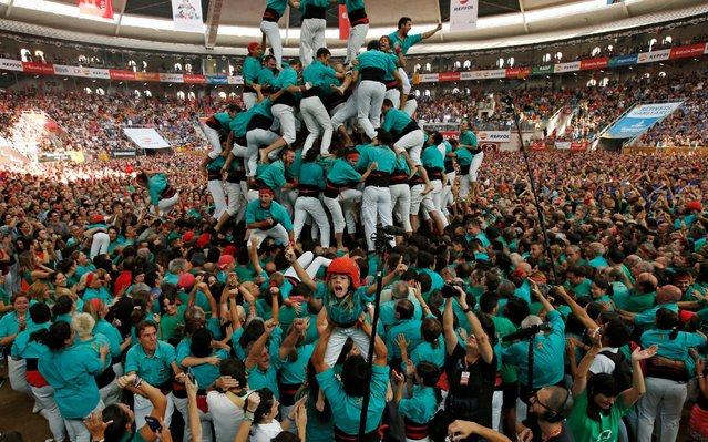 """Castellers de Vilafranca celebrate after forming a human tower called """"castell"""" during a biannual competition in Tarragona city, Spain, October 2, 2016. (Photo by Albert Gea/Reuters)"""