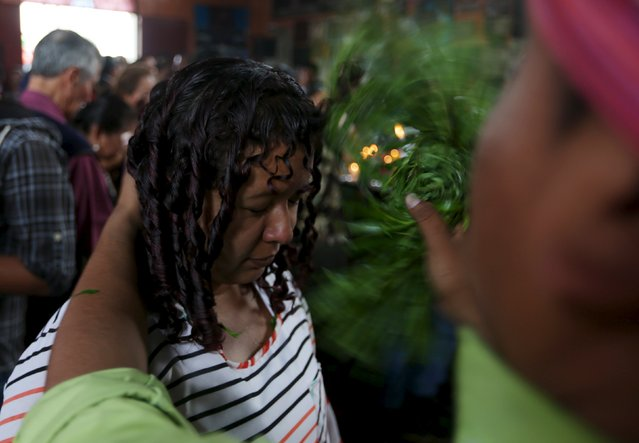 A woman receives a traditional cleansing in the church of San Simon in Iztapa, Chimaltenango, Guatemala, October 28, 2015. (Photo by Jorge Dan Lopez/Reuters)