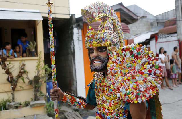 "A penitent in a costume made of candy wrappers takes part in a procession for the Moriones Festival during Holy Week in Mogpog town on Marinduque island, central Philippines, on March 27, 2013. During the festival, masked and costumed penitents called ""Moriones"" dress in attire that is the local interpretation of what Roman soldiers wore during biblical times. (Photo by Erik De Castro/Reuters /The Atlantic)"