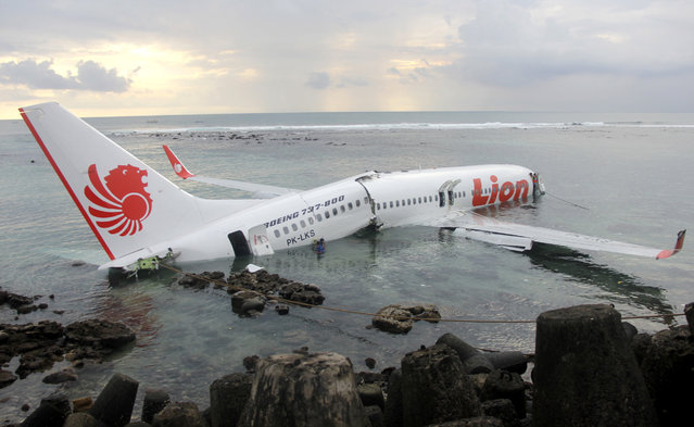 In this photo released by Indonesian Police, the wreckage of a crashed Lion Air plane sits on the water near the airport in Bali, Indonesia on Saturday, April 13, 2013. The plane carrying more than 100 passengers and crew overshot a runway on the Indonesian resort island of Bali on Saturday and crashed into the sea, injuring nearly two dozen people, officials said. (Photo by AP Photo/Indonesian Police)