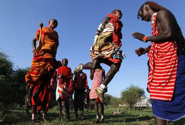 Maasai morans sing traditional songs and jump before the Maasai Olympics 2014 at the Sidai Oleng wildlife sanctuary at the base of Mt. Kilimanjaro near the Kenya-Tanzania border in Kajiado December 13, 2014. (Photo by Thomas Mukoya/Reuters)
