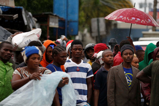 People wait to cross a bridge as the river rises due to the rains caused by Hurricane Matthew passing through Port-au-Prince, Haiti, October 4, 2016. (Photo by Carlos Garcia Rawlins/Reuters)