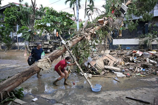 Residents walk under an uprooted tree next to an overturned vehicle (behind) and debris in a residential area in Marikina City, suburban Manila, on November 13, 2020, a day after Typhoon Vamco hit the capital area bringing heavy rains and flooding. (Photo by Ted Aljibe/AFP Photo)