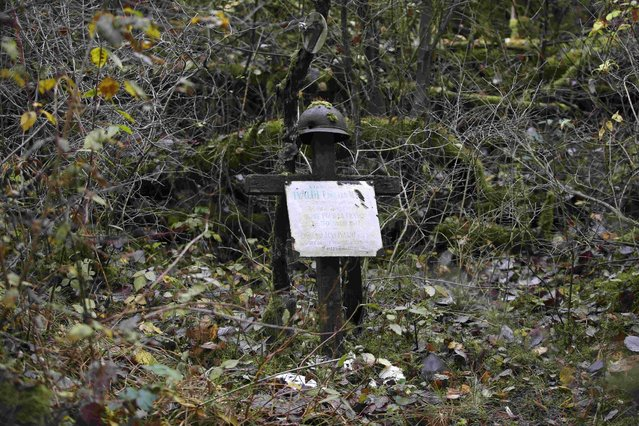 "General view of French WWI soldier Edouard Marius Ivaldi's battlefield grave memorial, a wooden cross with a battlefield helmet in Champagne, eastern France, November 3, 2015. The plaque which reads in part, ""In Memory of Edouard Marius Ivaldi, Corporal in the 7th Infantry  Regiment. Died for France on April 30, 1917"", was placed there by Ivaldi's father in 1919. (Photo by Charles Platiau/Reuters)"