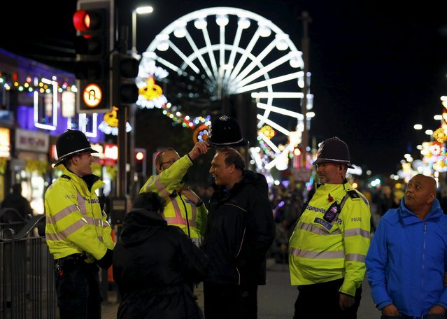 A man tries on a police officer's helmet during Diwali celebrations in Leicester, Britain November 11, 2015. (Photo by Darren Staples/Reuters)