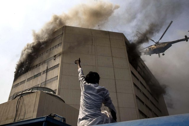 A bystander gestures to a helicopter and points to a man stranded by a fire at the Lahore Development Authority Plaza in Lahore, Pakistan. Helicopters were used to rescue stranded victims from the roof of the building, but at least five people plunged to their deaths from the burning building. (Photo by Daniel Berehulak/Getty Images)