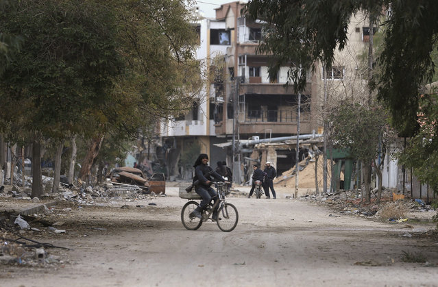 A rebel fighter carrying his weapon rides a bicycle along a street in Jobar, a suburb of Damascus, December 22, 2014. (Photo by Bassam Khabieh/Reuters)