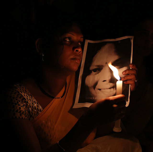 An Indian transgender holds a portrait of a victim of transphobia and participates in a candlelight vigil to mark Transgender Day of Remembrance in Hyderabad, India, Friday, November 20, 2015. The day is marked to remember victims of transphobia and to highlight violence and discrimination endured by the transgender community. (Photo by Mahesh Kumar A./AP Photo)
