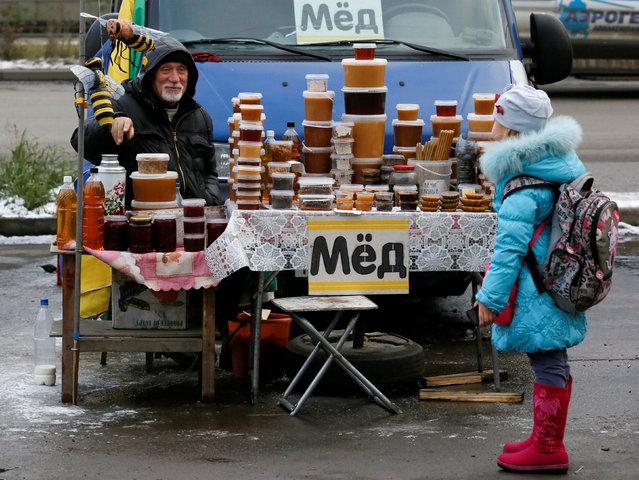 Honey vendor talks to a girl at a street market in Krasnoyarsk, Russia, October 17, 2016. (Photo by Ilya Naymushin/Reuters)