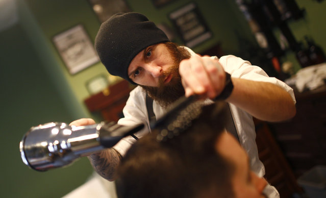 "Alex ""Torreto"" Vellios, a 26-year old Greek-born barber drys the hair of a customer at his Torreto barber shop in Frankfurt January 6, 2015. (Photo by Kai Pfaffenbach/Reuters)"