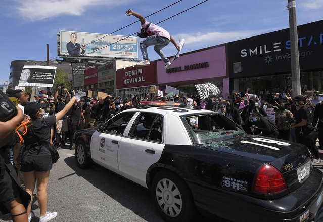 A demonstrator jumps on a police car during a protest over the death of George Floyd, Saturday, May 30, 2020, in Los Angeles. Protests were held throughout the country over the death of George Floyd, a black man who died after being restrained by Minneapolis police officers on May 25. (Photo by Mark J. Terrill/AP Photo)