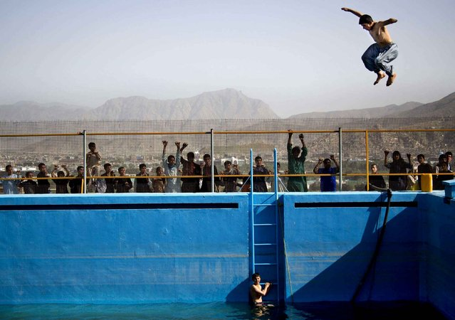 A young Afghan man jumps from a diving board into a swimming pool on a hill overlooking Kabul, Afghanistan, on May 17, 2013. The swimming pool build by the Soviets more then 30 years ago has rarely been used caught instead in the middle of decades of war. (Photo by Anja Niedringhaus/AP Photo)