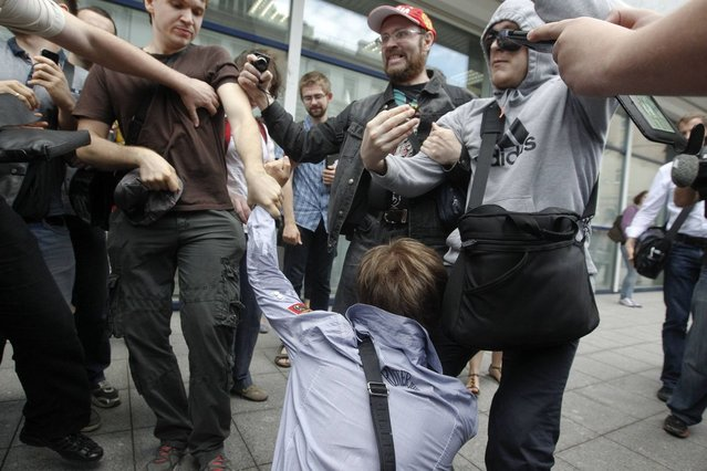 """People attack a gay rights activist during a protest against a proposed new law termed by the State Duma, the lower house of Parliament, as """"against advocating the rejection of traditional family values"""" in central Moscow June 11, 2013. (Photo by Maxim Shemetov/Reuters)"""