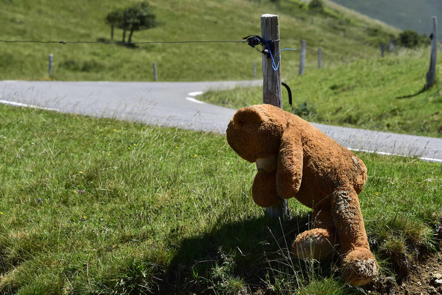 A teddy bear is hanged as people wearing tee- shirts bearing slogans against wolves and bears, gather on the first day of a protest against bears around Lers' pond in Ariege, on July 4, 2020. About 2,000 breeders, elected officials, agricultural trade unionists and hunters gather on July 4, 2020, to protest against the replacement of a bear killed in early June 2020 and calling for the end of bear releases. (Photo by Georges Gobet/AFP Photo)