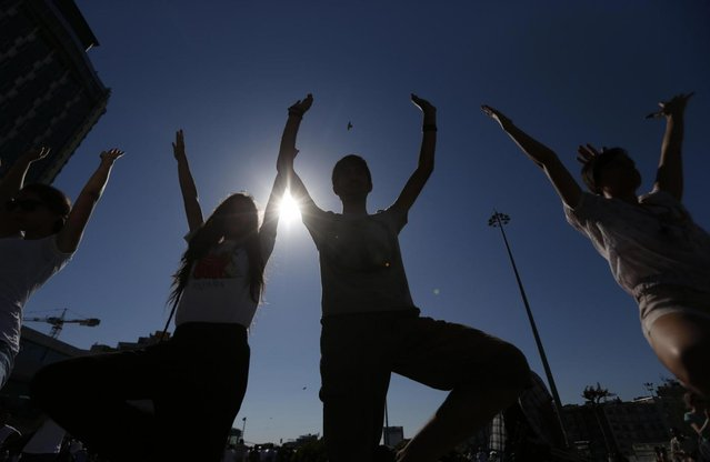Young people silhouetted against the sun practice yoga during a silent protest at Taksim Square in, Istanbul, Turkey, Wednesday, June 19, 2013. After weeks of sometimes-violent confrontation with police, Turkish protesters have found a new form of resistance: standing still and silent. (Photo by Petr David Josek/AP Photo)