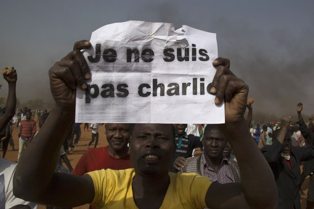 "A man holds a sign during a protest against Niger President Mahamadou Issoufou's attendance last week at a Paris rally in support of French satirical weekly Charlie Hebdo, which featured a cartoon of the Prophet Mohammad as the cover of its first edition since an attack by Islamist gunmen, in Niamey January 17, 2015. The sign reads as ""I am not Charlie"". (Photo by Tagaza Djibo/Reuters)"