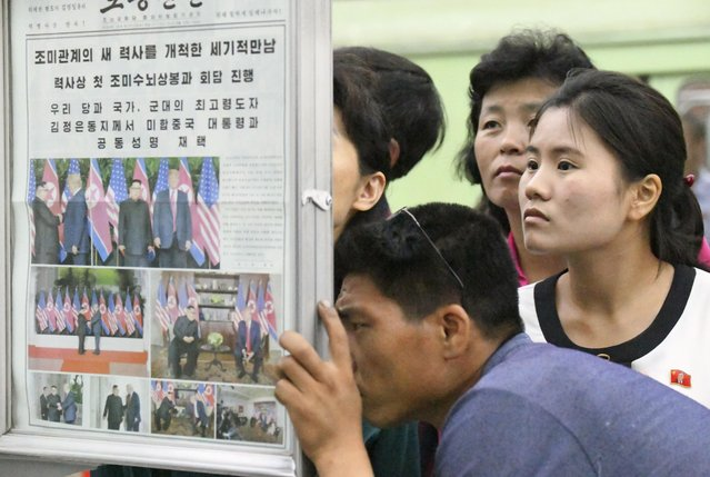 People look at the display of local newspaper reporting the meeting between North Korean leader Kim Jong Un and U.S. President Donald Trump, at a subway station in Pyongyang, North Korea Wednesday, June 13, 2018. The series of photos on the front page of the ruling workers' party newspaper showed something North Koreans never would have imagined just months ago, their leader Kim warmly shaking hands with Trump. (Photo by Minoru Iwasaki/Kyodo News via AP Photo)