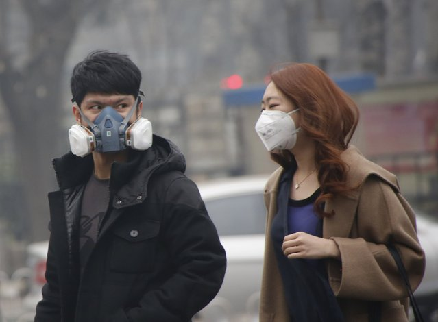 "A couple wearing masks make their ways in a shopping district amid heavy smog after the city issued its first ever ""red alert"" for air pollution, in Beijing, China, December 8, 2015. (Photo by Kim Kyung-Hoon/Reuters)"