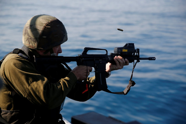 An Israeli officer fires a rifle as he takes part in a drill simulating the targeting of an infiltrated enemy vessel and the evacuation of a patrol boat, in the Mediterranean Sea off the coast of Ashdod, southern Israel November 8, 2016. (Photo by Amir Cohen/Reuters)