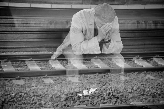 """Reflection"". Scene from a train station in Brussels, Belgium. This was truly a ""caught"" moment, un-staged. I call it ""Reflection"" because not only do we see someone in pain, in a moment of reflection, the effect of being shot through a window, and the resulting reflection, gives an almost ghost-like quality to the man, with the tracks suggesting something about his journey. In that regard, it has a powerful, almost conceptual quality. (Photo and caption by Adam Siers/National Geographic Traveler Photo Contest)"