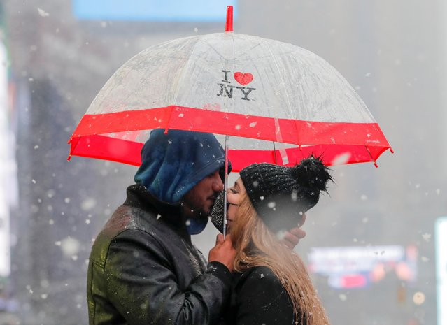 Eyad Alsous and Zugneily Santana, both from Florida, kiss under an umbrella as snow falls in Times Square, Manhattan, New York City, U.S., February 7, 2021. (Photo by Andrew Kelly/Reuters)
