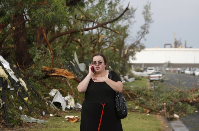 A worker at an industrial park talks on the phone among storm debris following a tornado in Sydney's southern suburb of Kurnell, December 16, 2015. (Photo by Jason Reed/Reuters)