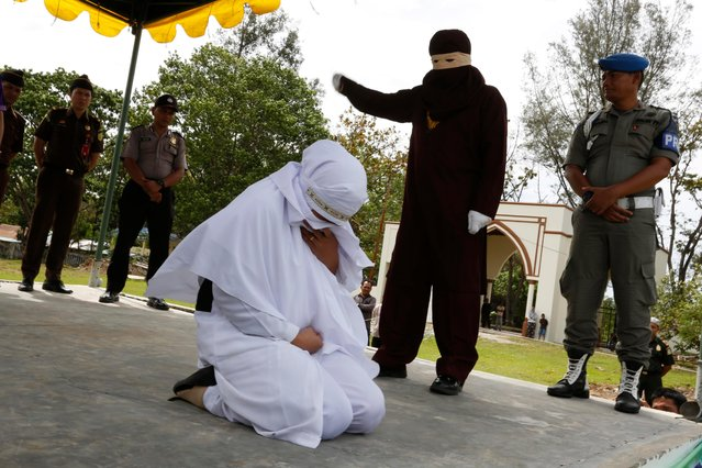 An Acehnese woman (L) faces a public caning punishment, for having a s*x relationship outside marriage, in Jantho, Aceh, Indonesia, 20 July 2018. Aceh is the only province in Indonesia that has implemented the Sharia law as a positive law and considers lesbian, gay, bisexual relationships and s*x outside of marriage as Sharia law violations. (Photo by Hotli Simanjuntak/EPA/EFE)