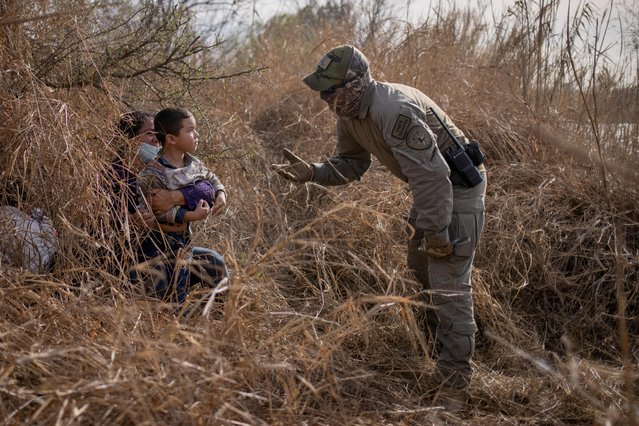 Texas State Trooper asks asylum-seeking migrants Edith and son Harbin Ordonez, 4, to come out of hiding after the Honduran nationals crossed the Rio Grande into the United States from Mexico on a raft in Penitas, Texas, March 9, 2021. About a dozen asylum-seeking migrants hid in the thick brush before being located by a U.S. Customs and Border Protection (CBP) Air and Marine Operations (AMO) helicopter and were taken into custody for processing. (Photo by Adrees Latif/Reuters)
