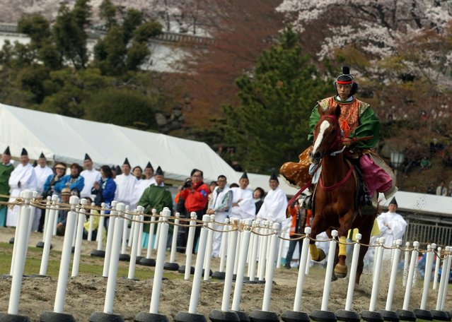 """A Japanese archer rides a horse while he performs traditional archery to entertain the gods during the Mitsuyama Taisai Festival of Itate Hyozu Shrine at front of the Himeji castle on April 3, 2013 in Himeji, Japan. The festival has been held once every 20 years since 1593. Priests of Itate Hyozu Shrine welcome all the gods across the country on the night of March 31st from the top of the """"three mountains"""" and treat with food for seven days to April 7 praying for peace and prosperity. (Photo by Buddhika Weerasinghe/Getty Images)"""
