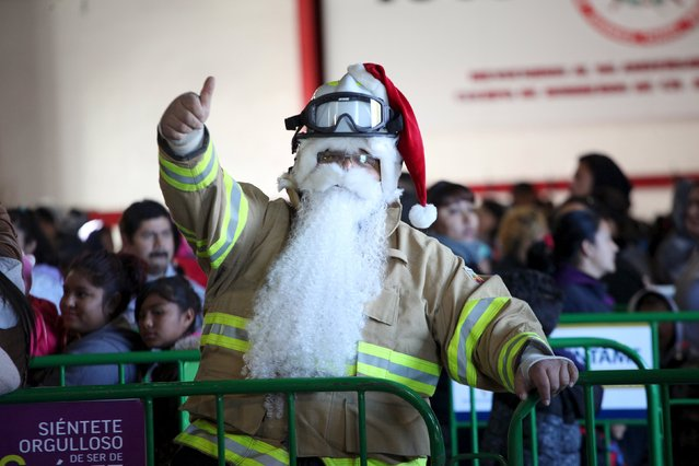 A firefighter, wearing a beard and a Santa Claus hat, gestures during the annual gift-giving event organised by firefighters in Ciudad Juarez, Mexico, December 24, 2015. The firefighters from Ciudad Juarez collect donated toys throughout the year for Christmas and hand them out to poor children on Christmas eve. (Photo by Jose Luis Gonzalez/Reuters)
