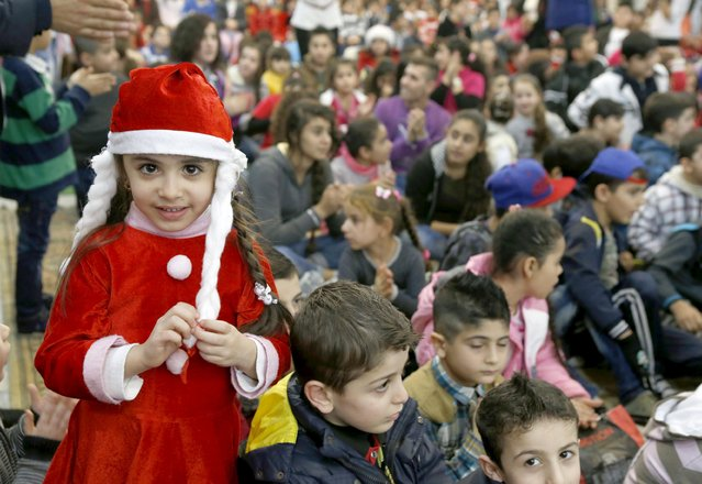 Iraqi and Syrian refugee children celebrate Christmas during a ceremony hosted by His Beatitude Archbishop Michel Qasarji, Diocese of Chaldeans in Babdaa, Lebanon December 19, 2015. (Photo by Mohamed Azakir/Reuters)