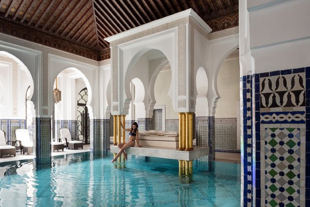 World's Greatest Swimming Pools: La Mamounia, Marrakech, Morocco. Below you, glazed Moroccan tiles shimmer in blues and greens. Above you, a dark wood ceiling vaults into a panel of stained-glass windows, with designs reflecting the ornate arches surrounding the pool. Around you, gilded columns frame the swim-up daybed, crowned by a marble platform. As traditional lanterns emit an amber sheen on the walls, you might ask: Is this heaven? (From $432). (Photo by La Mamounia)