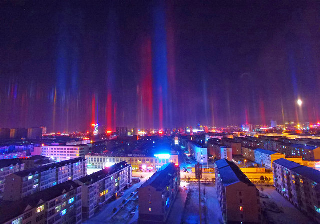 Sun pillars appeared in Xilinhot City, North China's Inner Mongolia Autonomous Region, on Wednesday, December 30, 2015. A sun pillar is a vertical shaft of light extending upward or downward from the sun. Typically seen during sunrise or sunset, sun pillars are formed when sunlight reflects off the surfaces of falling ice crystals associated with thin, high-level clouds. (Photo by Imaginechina/Splash News)