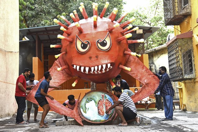 People are seen near a giant effigy resembling the Covid-19 coronavirus to be burned as a part of  Holika Dahan, or burning of Indian mythical demon Holika usually performed on the eve of Holi celebrations which is a popular Hindu spring festival of colours in Mumbai on March 28, 2021. (Photo by Sujit Jaiswal/AFP Photo)