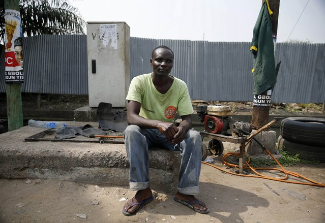 "Gabriel Taiwo, 42, an ethnic Yoruba Christian man and Vulcanizer, sits for a portrait at a roadside workshop in Ikoyi district in Nigeria's commercial capital Lagos January 21, 2015. ""I feel so bad that the election was postponed but there is nothing we can do now, we have to wait for the new dates – but I pray everything goes well"", Taiwo said. (Photo by Akintunde Akinleye/Reuters)"
