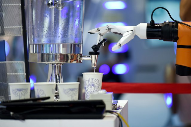 A robot arm demonstrates how to collect a cup of water at the 2018 World Robot Conference in Beijing on August 15, 2018. (Photo by Wang Zhao/AFP Photo)