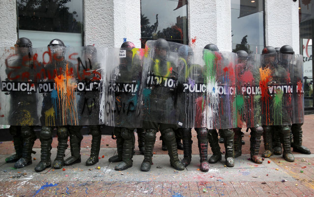 Riot police holding shields covered with paint thrown by protesters guard a public office in downtown Bogota, Colombia, Thursday, August 29, 2013. Students marched in support of farmers who have been blockading highways for more than 10 days for an assortment of demands that include reduced gasoline prices, increased subsidies and the cancellation of free trade agreements. (Photo by Fernando Vergara/AP Photo)