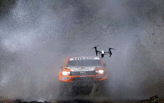 A drone with a camera follows Ronan Chabot of France as he drives his Toyota through the water during the Buenos Aires-Rosario prologue stage of Dakar Rally 2016 in Arrecifes, Argentina, January 2, 2016. (Photo by Marcos Brindicci/Reuters)