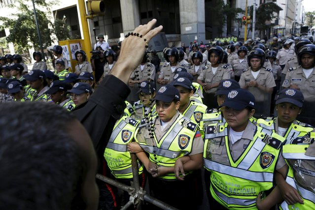 Catholic priest Jose Palmar, a supporter of Venezuela's opposition, holds a rosary towards the police as they block the access to the building housing the National Assembly in Caracas, January 5, 2016. (Photo by Marco Bello/Reuters)