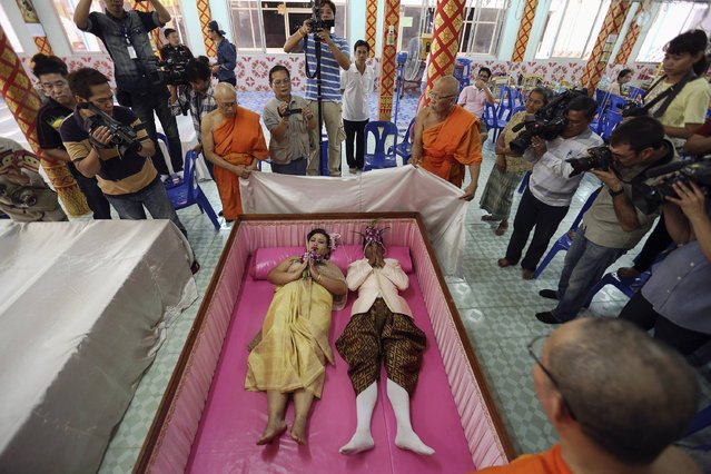 People take pictures and Buddhist monk chants as a groom and a bride lay inside a pink coffin during their wedding ceremony at Wat Takien temple in Nonthaburi province, on the outskirts of Bangkok February 14, 2015. (Photo by Damir Sagolj/Reuters)