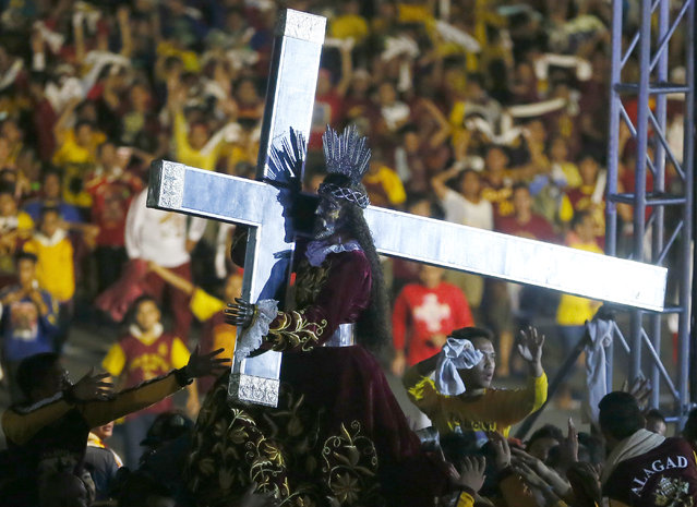 Catholic devotees mount the image of the Black Nazarene on a carriage as others jostle to get closer to kiss and rub with towels its cross during a raucous procession to celebrate its feast day in Manila, Philippines, Saturday, January 9, 2016. (Photo by Bullit Marquez/AP Photo)
